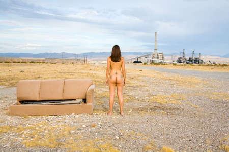 Nu une femme debout par un canapé abandonné Banque d'images - 3543137