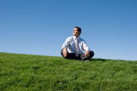 Businessman meditating on green grass Stock Photo - 3563144