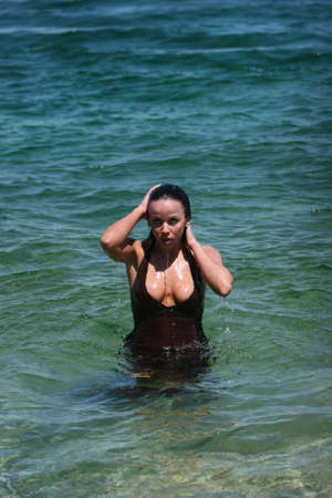 Sexy brunette girl with wet dress playing in the water