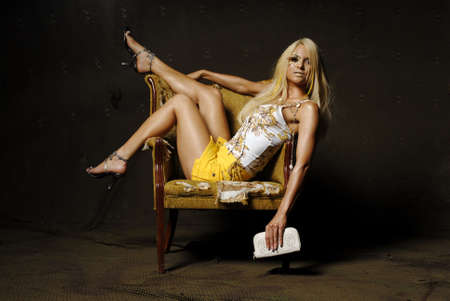 Sexy blond woman with makeup sitting on a chair