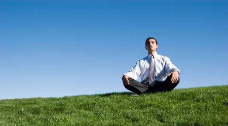 Businessman sitting on green grass photo