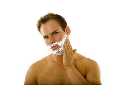haircut: Young male putting shaving cream on his face Stock Photo