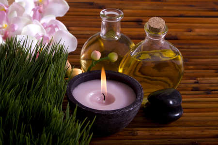 Relaxing candle, massage oils, pebbles and orchid flowers set on bamboo Stock Photo - 4000808
