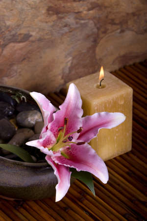Pink lily flower and burning candle set on bamboo for spa treatment Stock Photo - 4000799