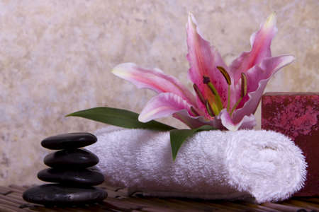 Balanced pebble rocks and pink lily flower on white towel for spa treatment Stock Photo - 4000791
