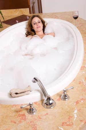 Sexy woman taking a bubble bath in the bathtub photo