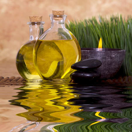 aromatherapy: Relaxing candle and massage oil bottles front of green grass Stock Photo