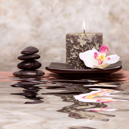 Spa candle and balanced stones with orchid photo