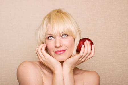 Beautiful blonde woman holding a red apple photo