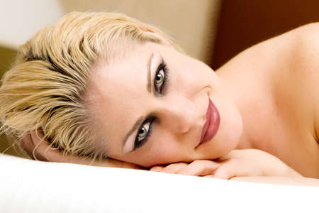 white sheet: Beautiful woman relaxing on bed Stock Photo