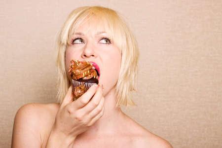 guilty pleasure: Mujer de comer un delicioso Cupcake de chocolate con chocolate frosting
