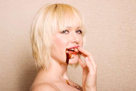 guilty pleasure: Mujer comiendo salsa de chocolate Foto de archivo