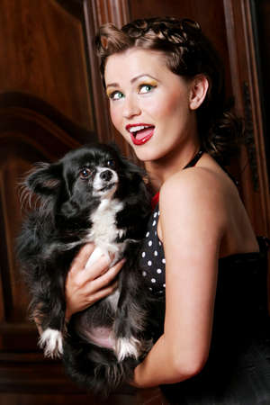 Pinup girl holding her pet dog