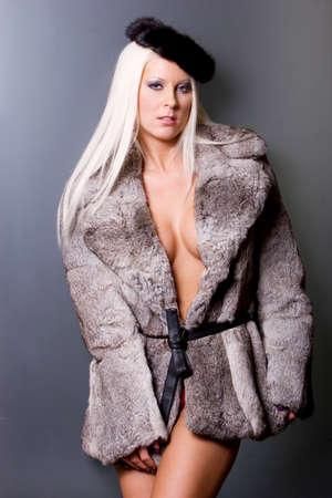 Sexy blonde woman in fur coat Imagens