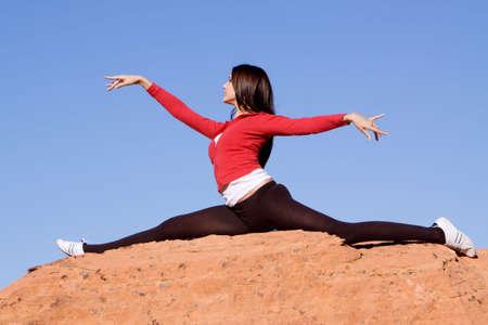 sportswoman: Gymnast doing split on red rocks Stock Photo