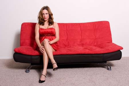 sofa: Pretty woman sitting on a sofa Stock Photo