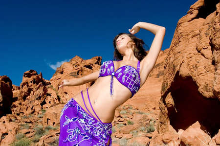 Beautiful young sexy belly dancer woman in desert