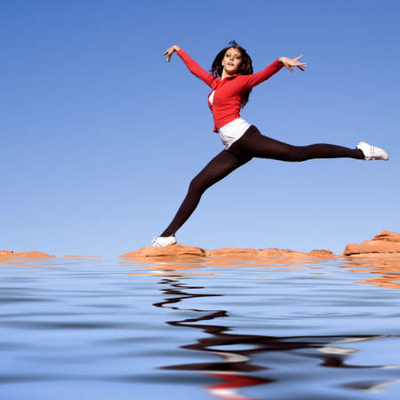 Beautiful young athletic woman jumping high photo
