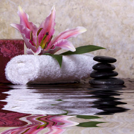 Balanced pebble rocks and pink lily flower on white towel for spa treatment Stock Photo - 4770587
