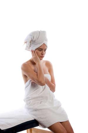 Beautiful young woman sitting on massage table
