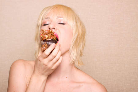guilty pleasure: Woman eating a delicious chocolate cupcake with chocolate frosting