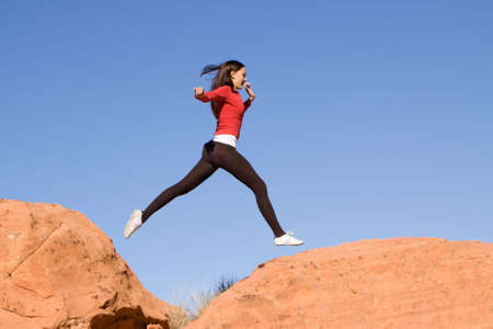 sportswoman: Beautiful young athletic woman running and jumping on red rocks
