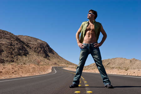 Handsome young man standing on road photo