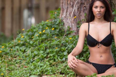 Brunette woman in bikini meditating outdoors photo