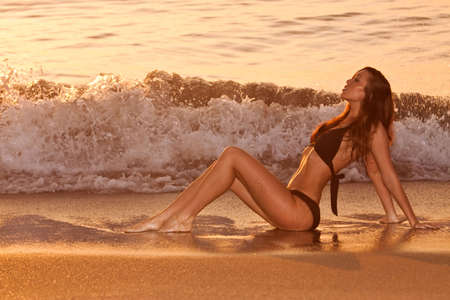 Sexy woman in bikini by the beach photo