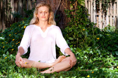 Blonde woman meditating in the lush garden photo
