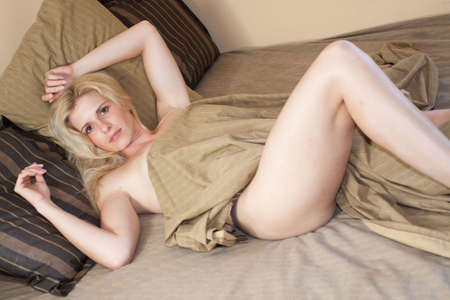 bed sheet: Sexy blonde woman lying on bed