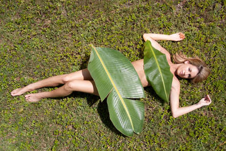 Sexy woman covered in banana leaves photo