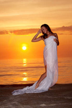 Beautiful woman by the ocean at sunset photo