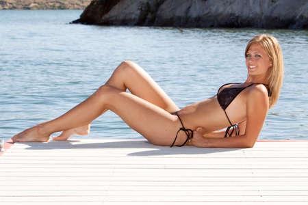 Sexy woman wearing a bikini by the lake photo