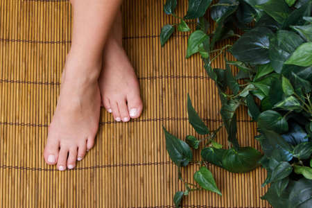 bamboo mat: Womans pedicured feet on bamboo mat Stock Photo