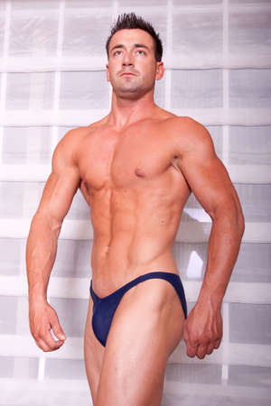 Muscular body builder showing his muscles photo
