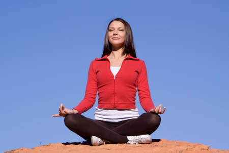 Young woman meditating on red rocks photo