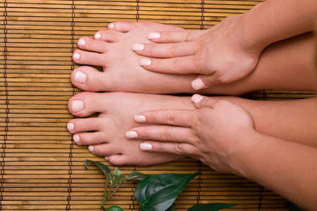handcare: Womans pedicured feet on bamboo mat Stock Photo