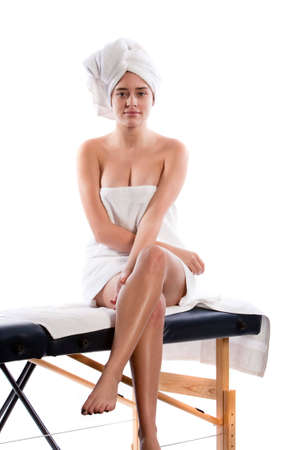 Beautiful young woman sitting on massage table photo
