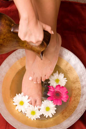 feet washing: Woman washing her feet in a bowl of water Stock Photo