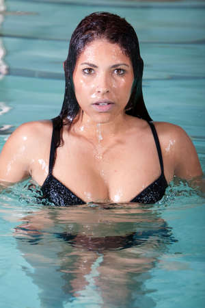 Sexy brunette woman swimming in the pool photo