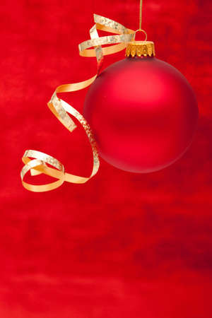 Red Christmas ornament with gold ribbon hanging Stok Fotoğraf