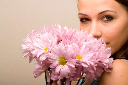 Pretty young woman smelling daisies Stock Photo - 6399704