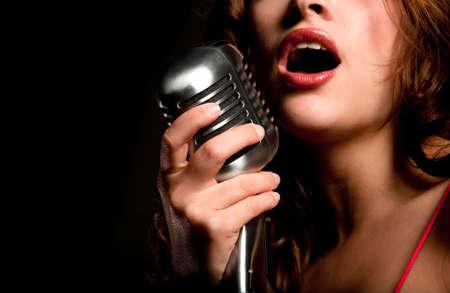 personas cantando: Bella cantante cantando con un micr�fono retro