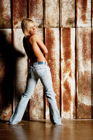 Sexy woman in blue jeans in front of a rusty panel Stock Photo - 6510338