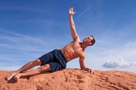 Young man doing yoga outdoors photo