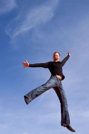 Young casual man jumping in the air photo