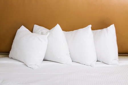 Clean white pillows and sheet on bed Imagens
