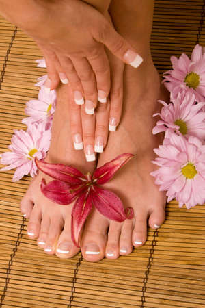 Womans hands and feet with flowers photo