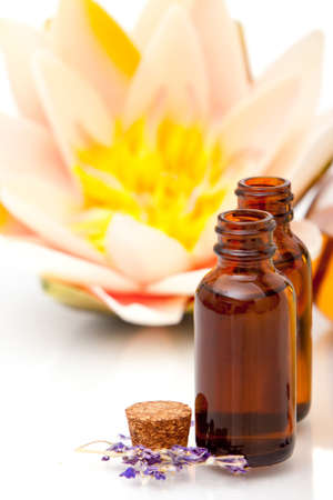 Massage oils and waterlily on white background